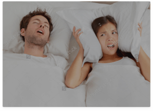 Male and female in bed man has mouth open snoring and female is holding pillow over her ears