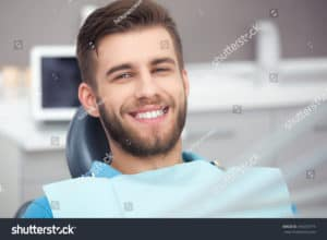 Man staring directly at screen with a white smile sat in a dentist chair