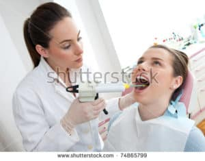 a woman having white fillings applied by a dentist