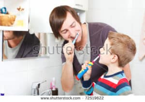 A man showing a child how to brush their teeth