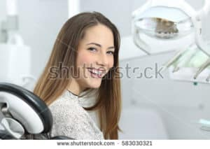 lady looking at camera and smiling sat in a dentist chair