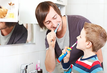 child brushing teeth with his dad
